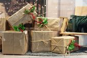 A Pile Of Large Christmas Gifts In Eco Wrapping With Holly Berries. Christmas Or New Year Time. Livi poster