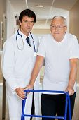 picture of zimmer frame  - Young handsome doctor helping an old man with his walker - JPG