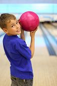 Smiling boy dressed in blue T-shirt holds pink ball in bowling club, stands with his back to camera