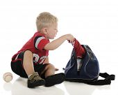 An adorable young preschooler pulling items from his sports bag, a baseball at his side.  On a white