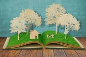 Paper cut of family symbol on old grass book  ( House,Tree,Mom,Dad,Child  )
