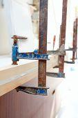 Carpenter screw clamp tools pressing wood slats and white glue