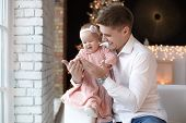 Man And Cute Baby Are Ready To Celebrate New Year. Happy Father Plays With His Infant Daughter Near  poster