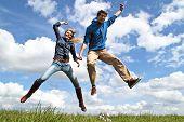 Joven pareja entusiasta saltar en el aire
