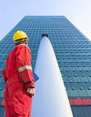 Building contractor looking up at  tall and imposing corporate office building with a lightshow on t