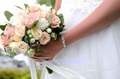 The Bride In A White Elegant Wedding Dress Is Holding A Beautiful Wedding Bouquet Of Different Flowe poster