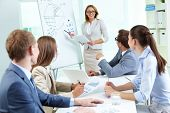 foto of enthusiastic  - Team members listening attentively to a cheerful business woman holding a presentation - JPG