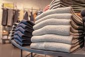A Stack Of Clothes In The Store, Pullovers And Sweatshirts Nicely And Neatly Stacked In Bundles On T poster