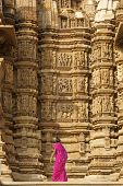 stock photo of kandariya mahadeva temple  - Tourist in pink sari looking at erotic carvings on the Kandariya Mahadeva Hindu Temple at Khajuraho Uttar Pradesh India - JPG