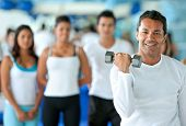stock photo of lifting weight  - man lifting free weights at the gym with a group of people behind him - JPG