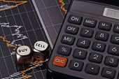 Dices Cubes With The Words Sell Buy, Calculator And Financial Chart As Background