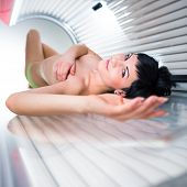 foto of uv-light  - Pretty young woman tanning her skin in a modern solarium - JPG