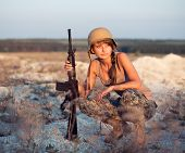 Young Female Soldier Dressed In A Camouflage With A Gun In The Outdoor