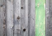 Background Texture Of Old Gray Weathered Wooden Lining Boards With One Green Painted Plank