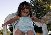 Girl Smiling On White Chair