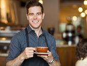 Portrait of happy waiter holding coffee cup while standing in cafeteria
