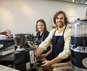 stock photo of apron  - Portrait of happy colleagues working in coffeeshop - JPG