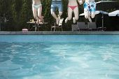 Four friends holding hands and jumping into pool