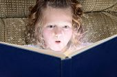 little girl enjoying magic of reading