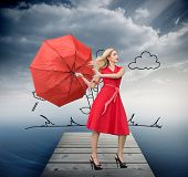 Composite image of beautiful woman posing with a broken umbrella with her leg raised