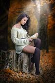 Young Caucasian sensual woman reading a book in a romantic autumn scenery. Portrait of pretty young