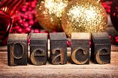 The word PEACE written with vintage wood printer blocks. Christmas message over old wood with traditional tree decorations behind.