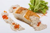 Fried halibut fillet with pepper sauce with salmon caviar and lettuce.