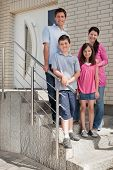 Happy Young Family Standing At Doorstep