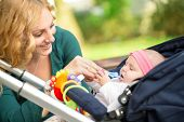 foto of teething baby  - Cheerful mother giving her baby toy for baby teething  - JPG