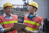pic of protective eyewear  - Two engineers in protective workwear standing and laughing outside of factory - JPG