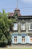 Old two-story wooden house with shutters and carving frames. Irkutsk