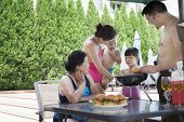 Smiling multi-generational family barbequing by pool on vacation