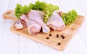 Raw chicken legs on wooden board on wooden table