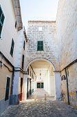Ciutadella old town narrow street with archway, Menorca, Spain.