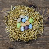 Straw nest full of candy covered easter eggs
