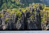 Huge limestone cliff coastline in Palawan with traditional Bangka boats, Philippines