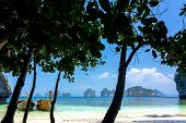 Tranquil tropical beach with tree silhouette and longtail boat in Koh Hong island, Pang Nga bay, Tha