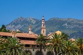 pic of blue-bell  - Catholic church bell tower among houses and palms and mountain on background under blue sky in Menton - JPG