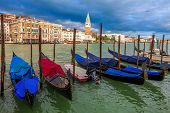 Gondolas on Grand Canal as traditional venetian buildings and San Marco campanile on background in V