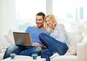 love, family, technology, internet and happiness concept - smiling happy couple witl laptop computer