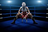 Boxing woman sitting alone in the boxing arena surrounded by blue lights