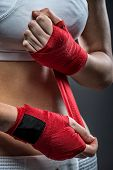 Boxing woman binds the bandage on his hand before training detail photo