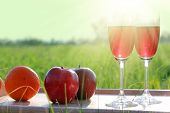 picnic - tabe with wine, wineglasses and fruits against sun