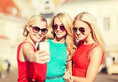 holidays and tourism, modern technology concept - beautiful girls taking picture in the city