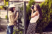 woman photographer take a photo of young woman with camera outdoor shot