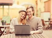 summer holidays, city, dating and technology concept - couple with laptop in cafe