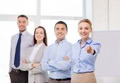 business and office concept - smiling handsome businesswoman with team in office pointing finger at