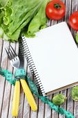 Cutlery tied with measuring tape and notebook with vegetables on wooden background