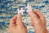 Hands Connect Puzzle Pieces Against Clouds