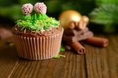 Tasty cupcake with butter cream, on  wooden table, on bright background